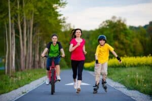 Active family – mother and kids running, biking, rollerblading