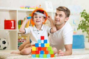 43213996-kid-boy-and-father-play-builders-in-children-room